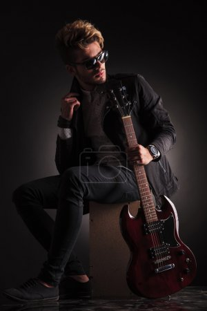 Photo for Side view of a young guitarist sitting and looking back while he holds his electric guitar , against black studio background - Royalty Free Image