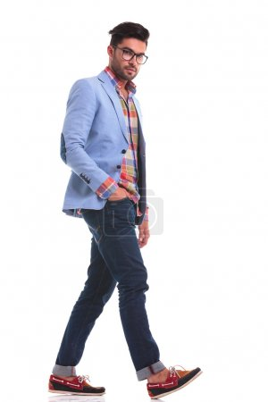 Photo for Handsome casual man looking at the camera while walking with his hand in pocket. - Royalty Free Image