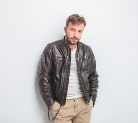 casual young man wearing leather jacket is standing