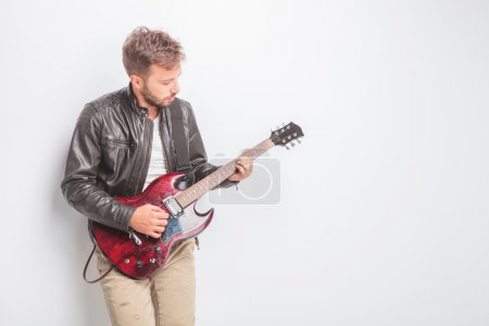 young guitarist in leather jacket playing
