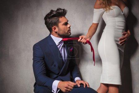 Photo pour Homme élégant en regardant son amant pendant qu'elle tire sa cravate et repart en studio - image libre de droit