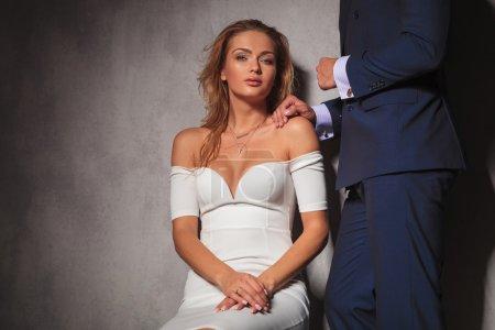 Photo pour Image de la découpe d'un couple élégant en studio, la femme est assise et l'homme tient sa main sur son épaule - image libre de droit