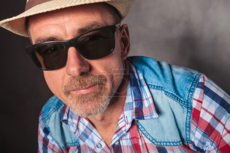 Head and shoulders of  mature man wearing hat and sunglasses
