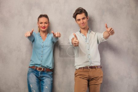 couple showing both thumbs up in studio background