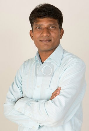An Indian or South Asian business executive with folded arms looking to camera. On grey background.