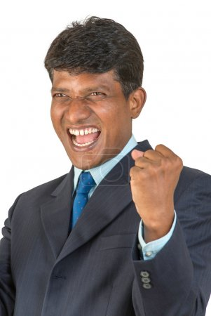 A thrilled Indian or South Asian business executive in a suit cheering a win or victory with a big shout and clenched fist. Isolated on white background.