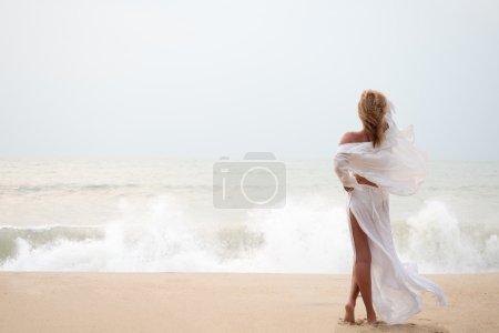 Photo pour Femme avec sarong sur la plage par une journée orageuse - image libre de droit