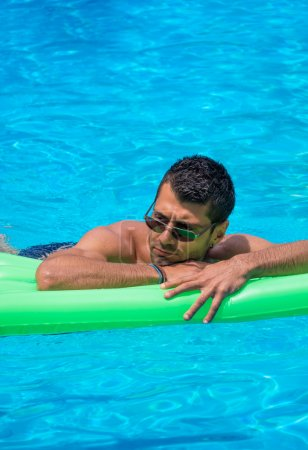 man relaxing on the air bed in the swimming pool.