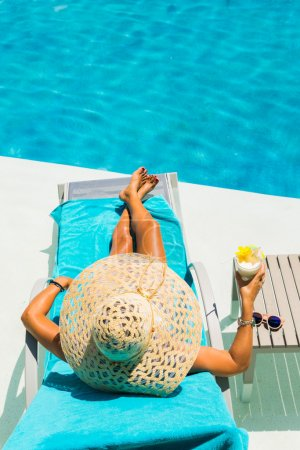 Woman at the poolside with pina colada cocktail