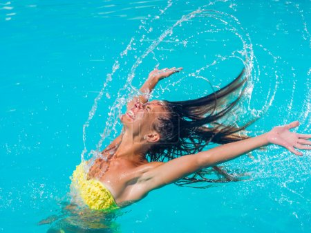 young tanned girl throwing wet hair back in swimming pool