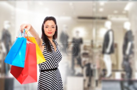 Young woman holding shopping bags in front of the ...
