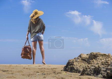 Photo pour Femme avec sac de voyage en cuir sur la plage en vacances - image libre de droit