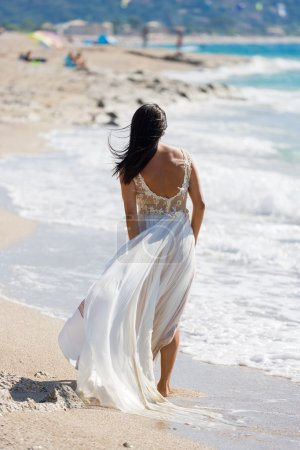 Beautiful young bride walking on the beach