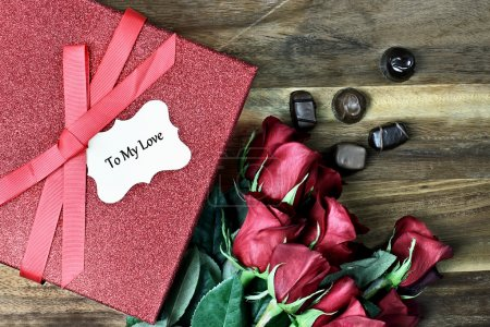Photo for Gift box with long stem red roses and chocolates over an old wooden background with room for copy space. - Royalty Free Image