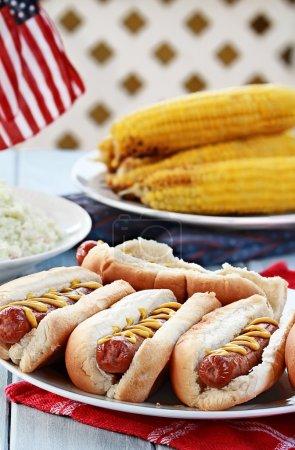 Photo pour Hotdogs à la moutarde, salade de chou et maïs sur une épi lors d'un pique-nique barbecue du 4 juillet . - image libre de droit