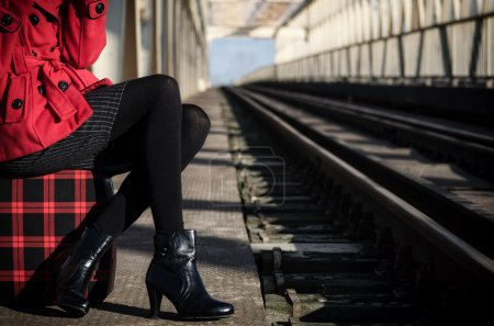 Elegant fashionable lady waiting for the train on the train stat