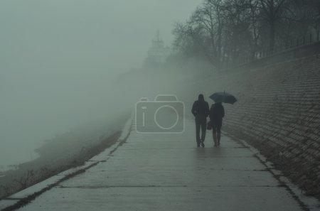 Couple walking beside river on misty winter day