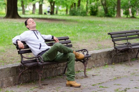 Young man sitting on the bench in the park and enjoying beautifu