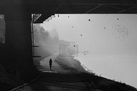 Silhouette de la jeune fille marche à côté de la rivière brumeux jour d'automne ensoleillé