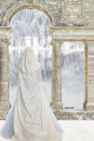 Portrait of cloaked woman by castle lake...
