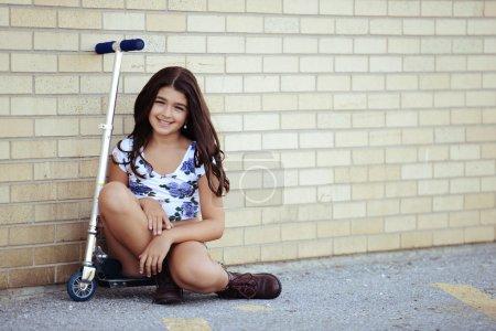 Photo pour Jeune fille assise sur scooter appuyé sur le mur - image libre de droit