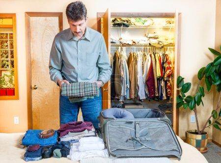Photo pour Un homme prépare sa valise pour un voyage - image libre de droit
