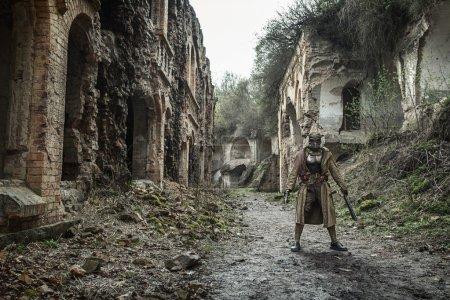 Photo pour La post-apocalypse nucléaire. Seul survivant en lambeaux et masque à gaz sur les ruines de la ville détruite - image libre de droit