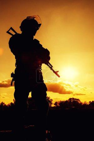 Photo pour Silhouette d'agent de police avec des armes au coucher du soleil - image libre de droit