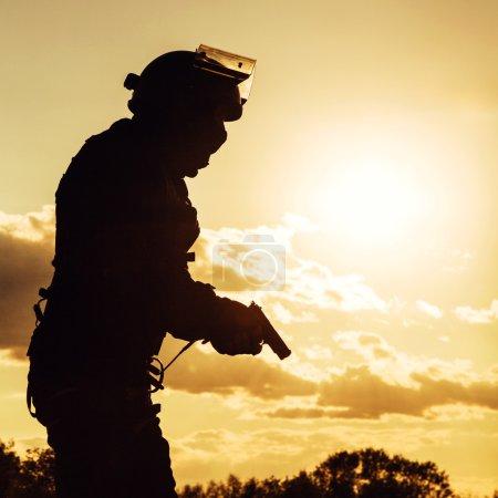 Photo pour Silhouette de policier avec pistolet au coucher du soleil - image libre de droit