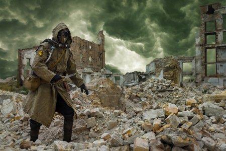 Photo pour Après l'apocalypse. Seul survivant en lambeaux et masque à gaz sur les ruines de la ville détruite - image libre de droit