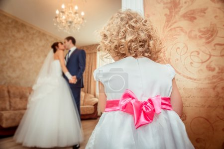 Little girl looking at the kissing bride and groom