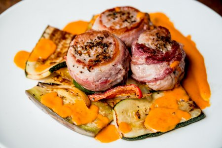 pieces of meat with grilled vegetables and sauce