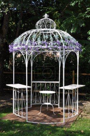 White metal pavilion in the green garden