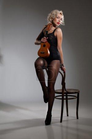 Photo pour Belle jeune femme blonde avec une petite guitare hawaïenne - image libre de droit