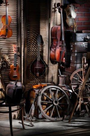 Photo pour Nature morte avec violons, violoncelle, valises et roues dans un style rural - image libre de droit