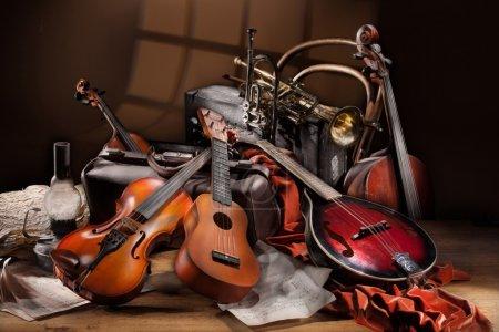 Photo pour Nature morte avec différents instruments de musique, des notes et des vieilles valises sur une table en bois - image libre de droit