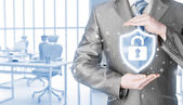 businessman holding shield with lock