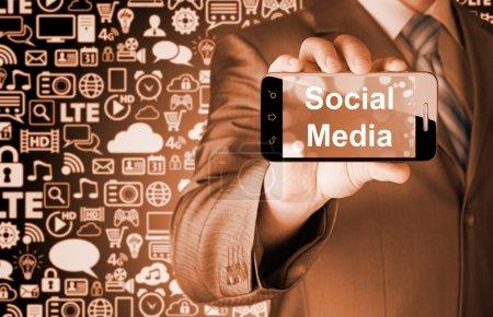 main de l'homme d'affaires détenant smartphone avec socail médias