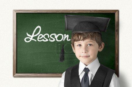 Photo pour Petit garçon joyeux sur le tableau noir à l'école - image libre de droit