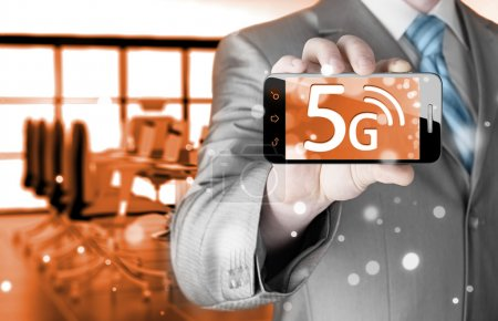 Businessman holding phone with 5G