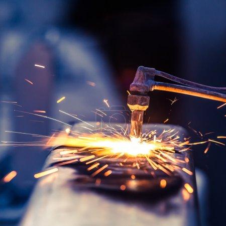 Photo pour Travailleur coupe tuyau d'acier en utilisant la torche en métal et installer une clôture au bord de la route - image libre de droit