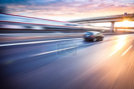 Auto fährt bei Sonnenuntergang auf Autobahn, Bewegungsunschärfe