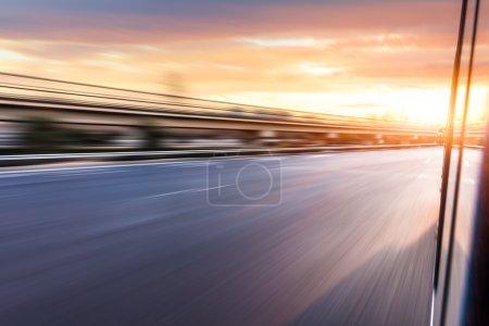 Photo pour Voiture conduisant sur l'autoroute au coucher du soleil, flou de mouvement - image libre de droit