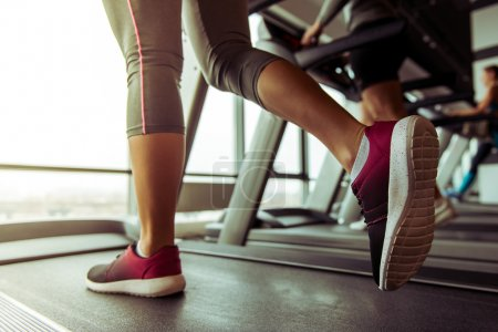 Photo for Legs of woman running on a treadmill in gym, close-up - Royalty Free Image