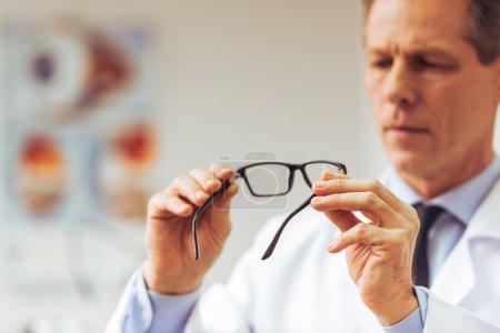 Photo pour Beau ophtalmologiste d'âge moyen tenant des lunettes et les examinant, se concentrant sur les lunettes, gros plan - image libre de droit