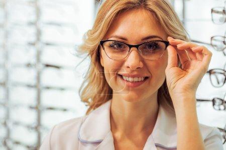 Photo pour Jeune belle ophtalmologiste féminine aux lunettes regardant la caméra et souriant, gros plan - image libre de droit