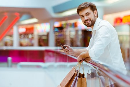 Photo for Handsome young man in white shirt holding shopping bags, using a smart phone and smiling while standing in mall - Royalty Free Image