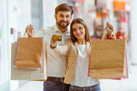 Photo pour Heureux beau jeune couple souriant, tenant des sacs à provisions et une carte de crédit tout en se tenant dans le centre commercial - image libre de droit