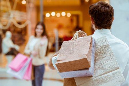 Photo pour Vue arrière d'un bel homme rencontrant sa belle femme dans un centre commercial. Les deux tenant des sacs à provisions - image libre de droit