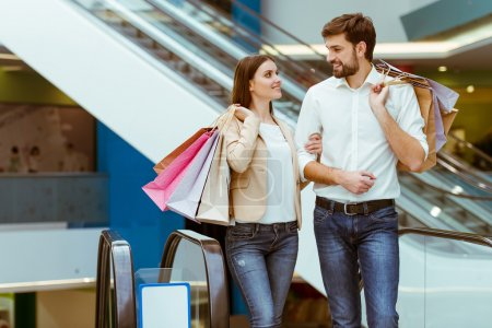 Photo for Happy beautiful young couple holding shopping bags and smiling while doing shopping in mall - Royalty Free Image